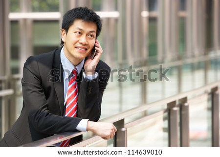 Portrait Of Chinese Businessman Outside Office On Mobile Phone