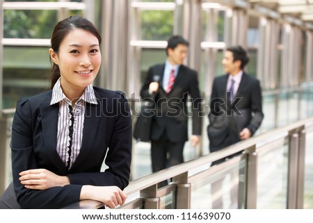 Portrait Of Chinese Businesswoman Outside Office With Colleagues In Background - stock photo