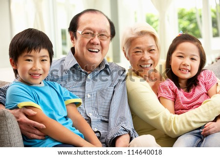 Portrait Of Chinese Grandparents With Grandchildren Relaxing At Home Together