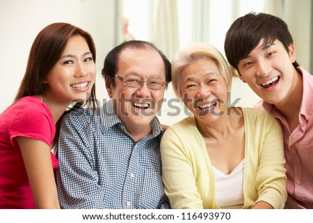 Portrait Of Chinese Parents With Adult Children Relaxing At Home Together - stock photo