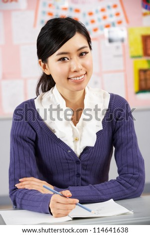 Portrait Of Chinese Teacher Sitting At Desk In School Classroom