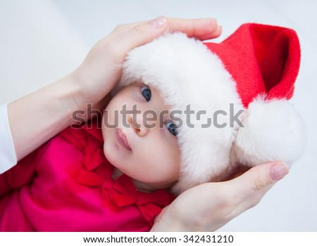Portrait of Christmas baby is lying on mothers hands - stock photo