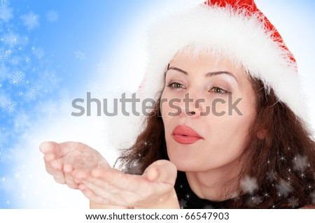 Portrait of christmas girl blows off snowflakes from the hands