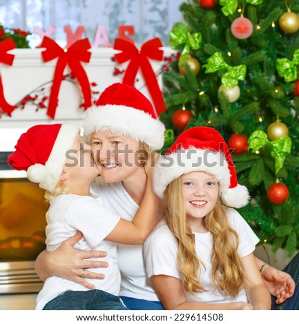 Portrait of Christmas happy family of three. Mother with children smiling and kissing, with Santa Hats, Christmas Tree and Chimney at background.