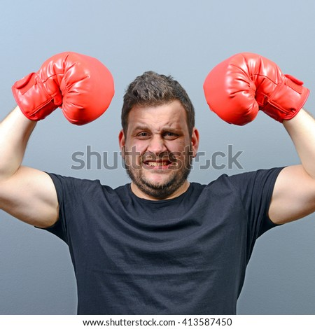 Portrait of chubby boxer posing with boxing gloves as a champion