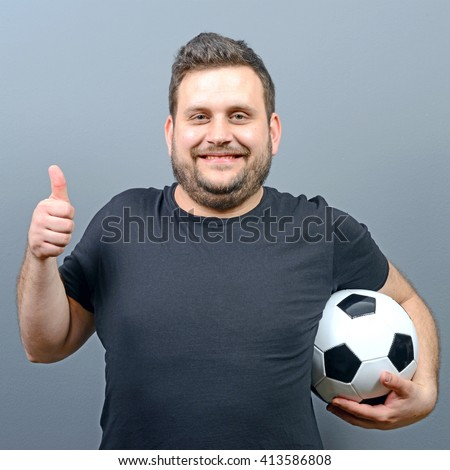 Portrait of chubby man holding football and showing thumb up - Football fan supporter or player concept