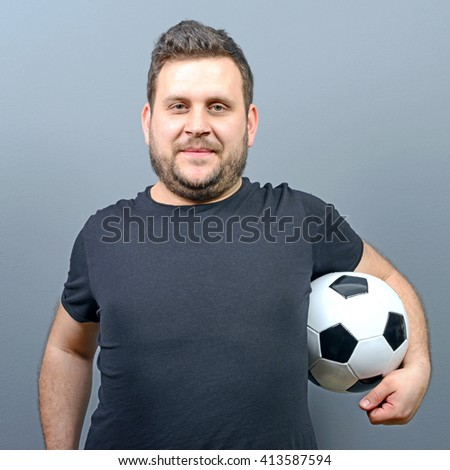 Portrait of chubby man holding football - Football fan supporter or player concept - stock photo