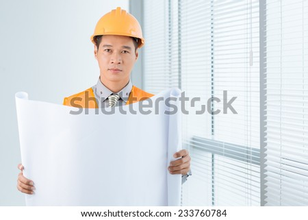 Portrait of civil engineer in a hardhat holding empty document - stock photo