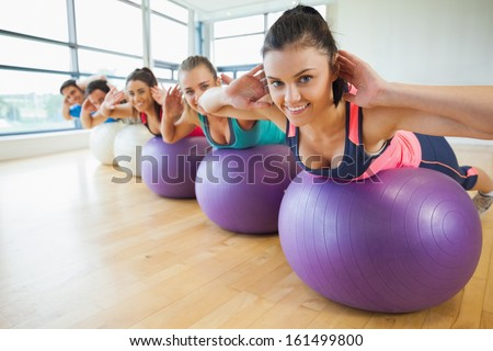 Portrait of class exercising on fitness balls in a row at the bright gym - stock photo