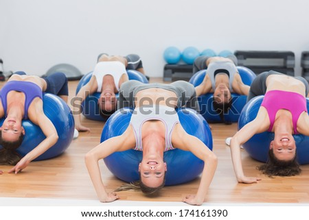 Portrait of class exercising on fitness balls in the gym - stock photo