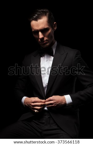 portrait of classy businessman in black suit with bowtie posing seated in dark studio background while closing his jacket and looking down - stock photo