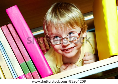 Portrait of clever boy looking from between books in library