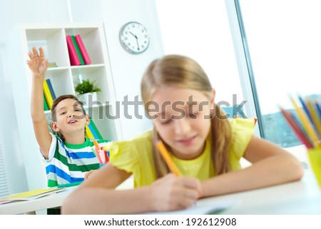 Portrait of clever schoolkid raising hand at lesson with his classmate in front - stock photo