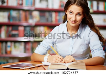 Portrait of clever student looking at camera while working in college library