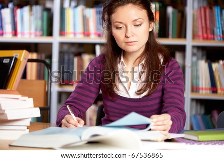 Portrait of clever student searching information for report in college library - stock photo