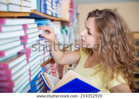 Portrait of clever student with books in college library
