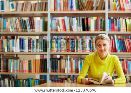 Portrait of clever student with open book looking at camera in college library - stock photo