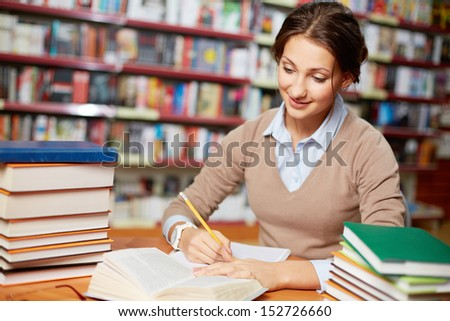 Portrait of clever student working in college library - stock photo