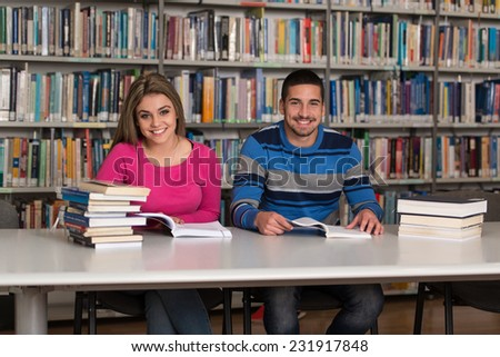Portrait Of Clever Students With Open Book Reading It In College Library - Shallow Depth Of Field - stock photo