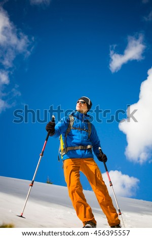 Portrait of climber on a background of mountains on a winter day.