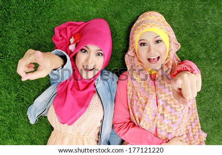 Portrait of close up two beautiful happy muslim woman lying on grass - stock photo
