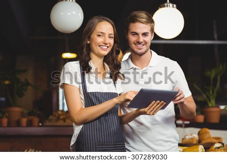 Portrait of co-workers holding a tablet at the coffee shop - stock photo