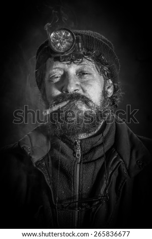 Portrait of coal miner with beard smoking cigar