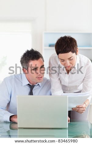 Portrait of colleagues comparing a blueprint document to an electronic one in an office - stock photo