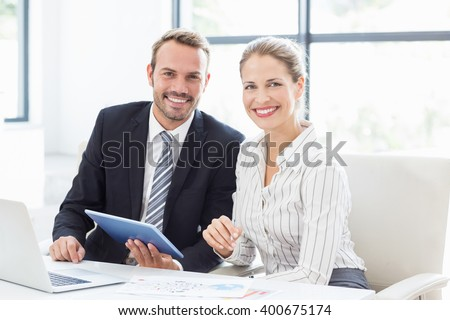 Portrait of colleagues using a digital tablet at desk in office