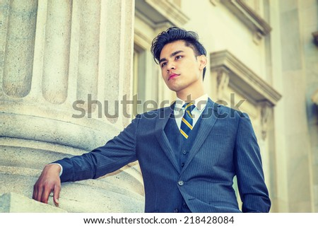 Portrait of College Student. Dressing in a black suit, patterned necktie,  a young handsome businessman is standing by a column, outside office building, thinking, looking forward.  - stock photo