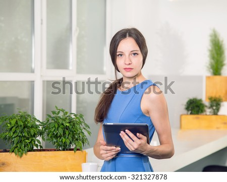 Portrait of college student in classroom. Girl student holding a digital tablet. Young student using a tablet computer in a room. Woman using his digital tablet. - stock photo