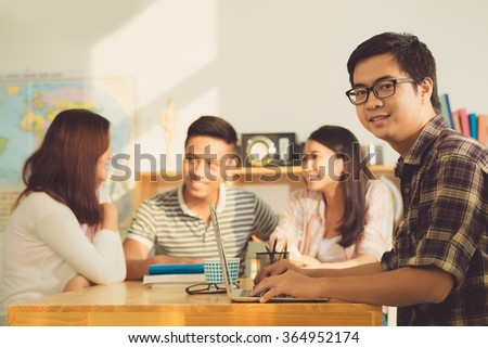 Portrait of college student working on laptop in classroom - stock photo