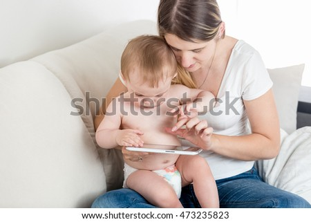 Portrait of concentrated baby boy and young mother touching screen on tablet PC