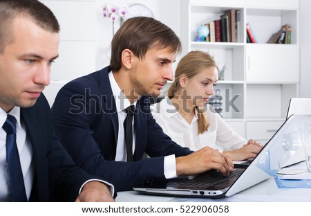 portrait of concentrated business man working on computer in office with work fellows