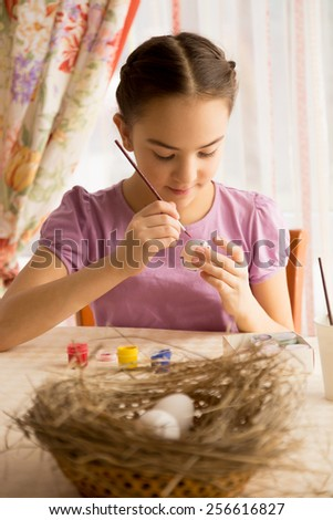 Portrait of concentrated girl painting Easter eggs at table