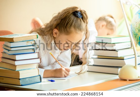 Portrait of concentrated schoolgirl surrounded by books doing homework - stock photo