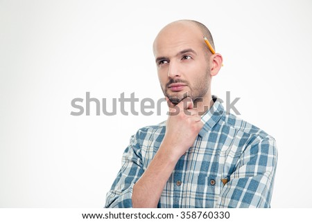 Portrait of concentrated thoughtful young man in checkered shirt with pencil behind ear isolated over white background - stock photo