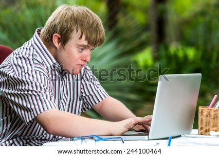 Portrait of concentrated young man with down syndrome working on laptop outdoors. - stock photo
