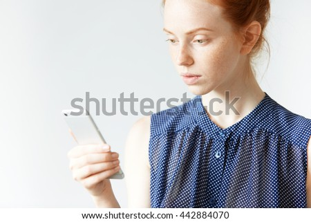 Portrait of concerned Caucasian redhead female using mobile phone, receiving a message from her boss via email, looking at the screen with serious expression while resting at home on the weekend - stock photo
