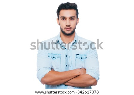 Portrait of confidence. Confident young Indian man keeping arms crossed and looking at camera while standing against white background - stock photo