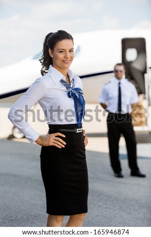 Portrait of confident airhostess with hands on hip smiling against pilot and private jet at airport terminal - stock photo