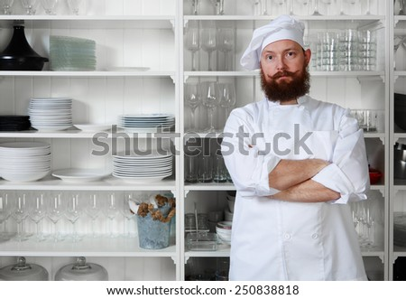 Portrait of confident and experienced chef cook standing with crossed army on big modern kitchen - stock photo