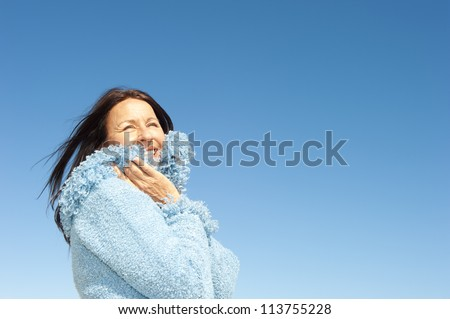 Portrait of confident and happy relaxed looking attractive senior woman enjoying active retirement in winter sun, isolated with blue sky as background and copy space.