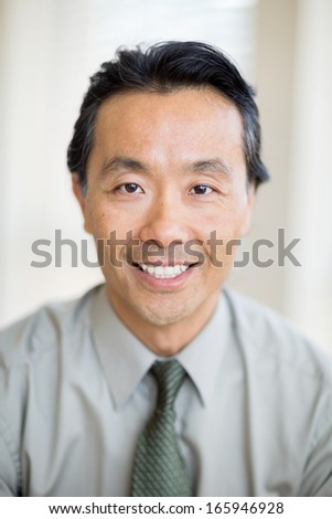 Portrait of confident Asian male cancer specialist smiling in hospital - stock photo
