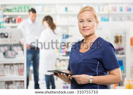 Portrait of confident assistant holding digital tablet while pharmacist and customer standing in background at pharmacy - stock photo