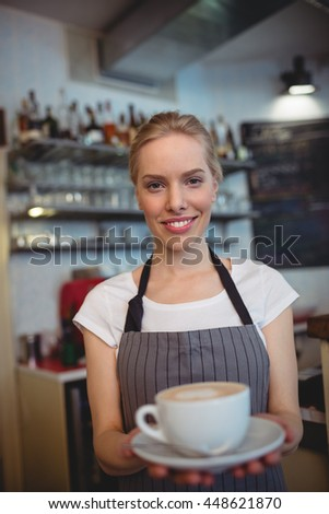 Portrait of confident attractive waitress serving coffee at shop - stock photo