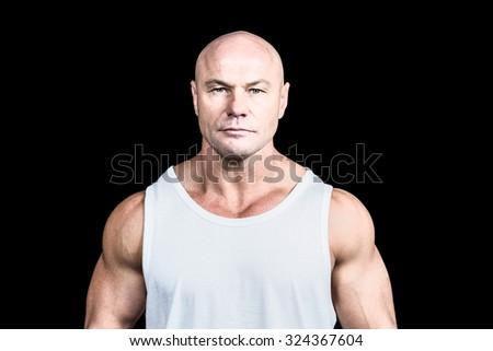 Portrait of confident bald man against black background - stock photo