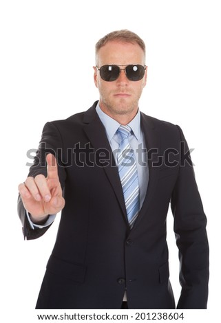 Portrait of confident bodyguard making stop gesture over white background - stock photo
