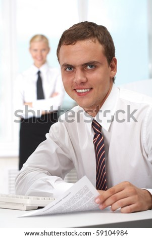Portrait of confident boss holding papers at workplace with executive secretary standing behind - stock photo