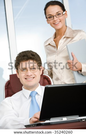 Portrait of confident boss sitting in workshop with smart businesswoman standing near by